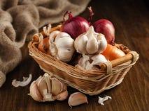 Zwiebel und Knoblauch in einem Korb auf dem Tisch Lizenzfreie Stockbilder