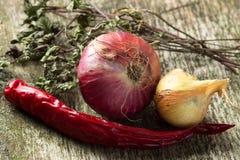 Zwiebel-und Paprika-Pfeffer mit Kräutern auf altem hölzernem Brett Stockfoto