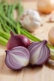 Zwiebelen-, Knoblauch- und Frühlingszwiebeln auf hölzerner Küche Stockfotos