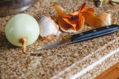 Zwiebelhülse zog Birne und Messer auf Marmortabelle ab lizenzfreie stockbilder