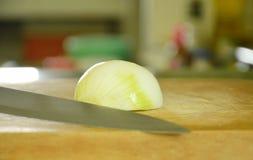 Zwiebelheftschnitt und -messer bereiten sich zum Kochen auf Hiebblock vor Lizenzfreie Stockfotos