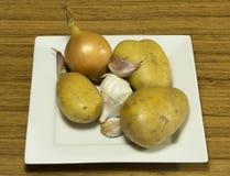 Zwiebeln auf weißer Platte Stockfotografie