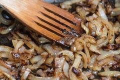 Zwiebeln, die in der Bratpfanne caramelizing sind lizenzfreie stockfotos