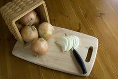 Zwiebeln in einem Korb auf einem Ausschnittvorstand. Lizenzfreie Stockfotografie