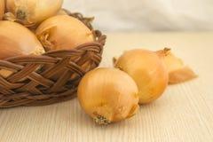 Zwiebeln in einem Korb auf einem Holzfuß Lizenzfreies Stockbild