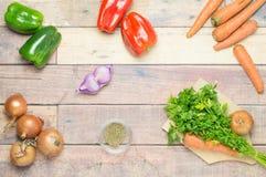 Zwiebeln, Pfeffer, Karotten, Knoblauch, Petersilie kochfertig auf dem Tisch Stockfoto