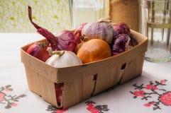 Zwiebeln und Knoblauch in einer Kiste Stockbilder