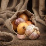 Zwiebeln und Knoblauch in einer Tasche des groben Stoffes auf dem Tisch Lizenzfreies Stockbild