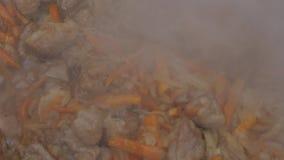 Zwiebeln und Knoblauch werden in einer Wanne mit Fleisch gebraten Kochen des angebratenen Fleisches mit Gemüse Langsame Bewegung stock video