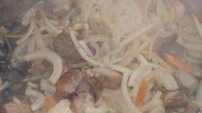 Zwiebeln und Knoblauch werden in einer Wanne mit Fleisch gebraten Kochen des angebratenen Fleisches mit Gemüse Langsame Bewegung stock footage