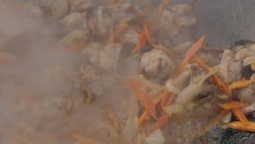 Zwiebeln und Knoblauch werden in einer Wanne mit Fleisch gebraten Kochen des angebratenen Fleisches mit Gemüse Langsame Bewegung stock video footage