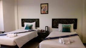 Zwilling gebetteter Raum Gehen Sie mit der weißen Bettwäsche zu Bett, verziert mit Kissen und blauem Bettläufer stockfotografie