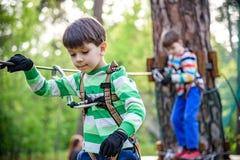 Zwilling st?rt, im Erlebnispark zu klettern ist ein Platz, der eine gro?e Vielfalt von Elementen, wie kletternden ?bungen des Sei stockfotos