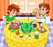 Zwillinge bereiten einen grünen Salat zu. Lizenzfreie Stockfotos