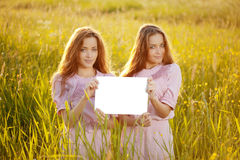 Zwillinge, die draußen weißes leeres Plakat halten Lizenzfreies Stockfoto