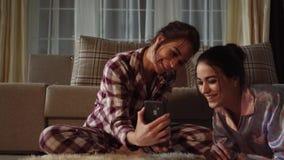 Zwillinge, die etwas lustig auf Smartphone aufpassen und auf dem Hintergrund des gemütlichen Wohnzimmers lachen Verhältnis-Schwes stock footage