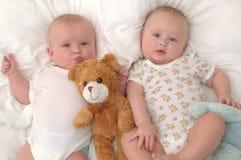 Zwillinge, die mit ihrem Teddybären liegen stockbilder