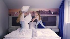 Zwillinge, die mit Kissen auf Bett kämpfen stock video footage