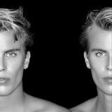 Zwillinge Zwei halbe Gesichter von blonden Männern auf schwarzem Hintergrund Stockfotografie