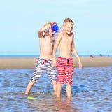 Zwillingsbrüder, die auf dem Strand spielen Stockfotos