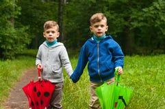 Zwillingsbrüder mit Regenschirmen Stockfotos
