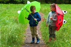 Zwillingsbrüder mit Regenschirmen Lizenzfreies Stockbild