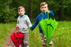 Zwillingsbrüder mit Regenschirmen Stockbild