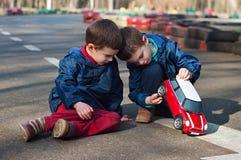 Zwillingsbruderspiel mit einem Spielzeugauto Stockfotografie