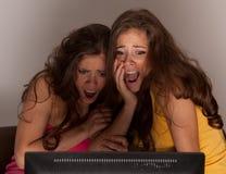 Zwillingschwestern, die einen Horrorfilm auf Fernsehapparat überwachen stockbilder