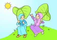 Zwillingsmädchen, das mit großen Blättern spielt Stockfoto