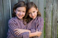 Zwillingsmädchen kleidete oben an, wie siamesisch mit seinem Vaterhemd stockbild