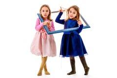 Zwillingsmädchen macht glückliche Ausdrücke mit Bilderrahmen Lizenzfreie Stockfotografie