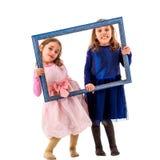 Zwillingsmädchen macht glückliche Ausdrücke mit Bilderrahmen Stockbilder