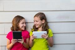 Zwillingsschwestermädchen, die mit dem Tabletten-PC glücklich auf weißer Wand spielen Stockfotos