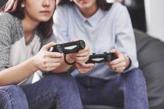 Zwillingsschwesterschwestern spielen auf der Konsole Mädchen halten Steuerknüppel in ihren Händen und Spaß zu haben stockfotos
