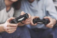 Zwillingsschwesterschwestern spielen auf der Konsole Mädchen halten Steuerknüppel in ihren Händen und Spaß zu haben stockfotografie