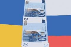 Zwischen den Flaggen von Russland und Ukraine sind Banknoten von Euro 20 Lizenzfreies Stockfoto