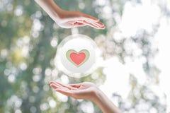 Zwischen den Händen das Symbol von Herzen Stockfotos
