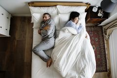 Zwischen verschiedenen Rassen Paare auf der Bettfrau, welche die ganze Decke nimmt Lizenzfreie Stockfotos