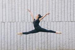 Zwischen verschiedenen Rassen weibliches Tänzerspringen lokalisiert auf einer grauen Wand Lizenzfreies Stockfoto
