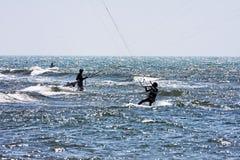 Zwischen Wellen und Wind in einem rauen Meer, üben Athleten, an einem schönen Frühlingstag kitesurfing stockfotografie