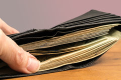 Zwitek dolarów amerykańskich rachunki w czarnym portflu na stole Obraz Stock