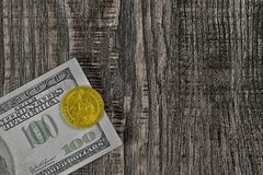 Zwitki sto dolarowych rachunków i jeden złocisty dolar od wierzchołka na drewnianym tle obraz stock