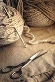 Zwitki szara przędza, starzy nożyce i haczyk na szarej tkaninie, Obrazy Royalty Free
