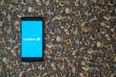 Zwitschern Sie Logo auf Smartphone auf Hintergrund von kleinen Steinen Lizenzfreie Stockfotografie