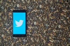 Zwitschern Sie Logo auf Smartphone auf Hintergrund von kleinen Steinen Stockbilder