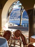 Zwitserland - Morcote, lijst en stoelen onder boog. Stock Fotografie