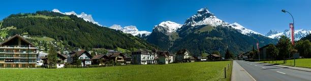 Zwitsers dorp, weg en alpiene bergen Royalty-vrije Stock Fotografie