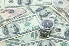 Zwitsers horloge op stapel van Amerikaanse dollarbankbiljetten Stock Foto