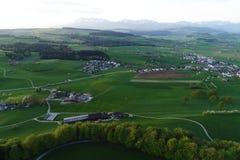 Zwitsers laagland met dorpen, landbouwbedrijven en de Alpen op de achtergrond royalty-vrije stock foto